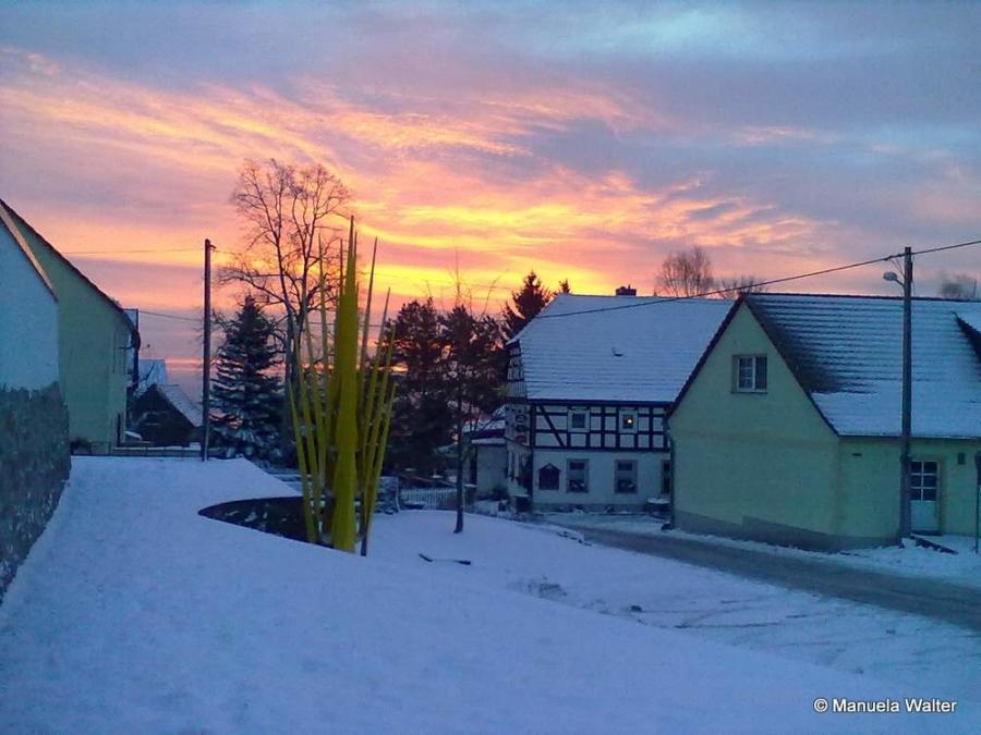 Das Foto von Manuela Walter entstand im Ortsteil Jauernick-Buschbach und zeigt die Goldene Ähre und den Berggasthof, während über dem Berzdorfer See (nicht im Bild) die Sonne aufgeht. Das Foto war zum Fotowettbewerb 2016