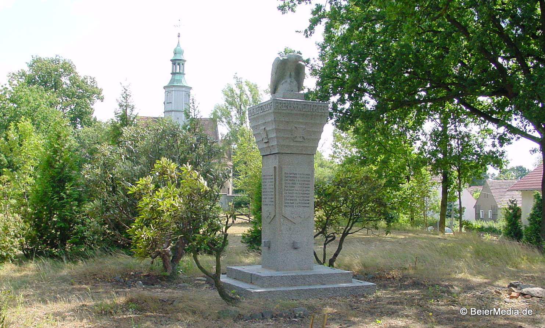 Kriegerdenkmal in Gersdorf, dahinter die Kirche