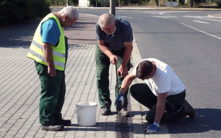Bauhof-Mitarbeiter beim Reinigen der Einlaufrinnen