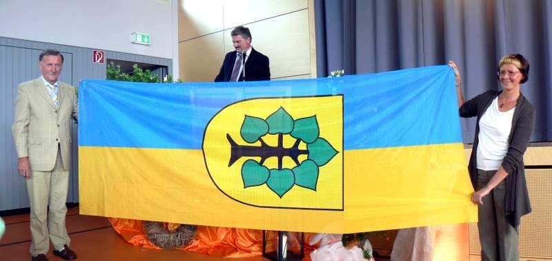 Hartmut Rohne, Bürgermeister Thomas Knack und Dr. med. Kerstin York übergeben die Markersdorfer Fahne in Erligheim. (Fotomontage)