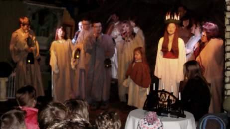 Die heilige Lucia mit dem Kerzenkranz auf der Bühne der Festscheune des Markersdorfer Dorfmuseums.